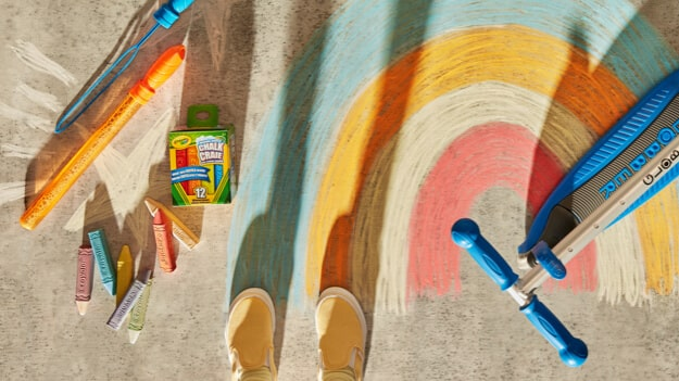 A kid standing over a chalk drawing of a rainbow.