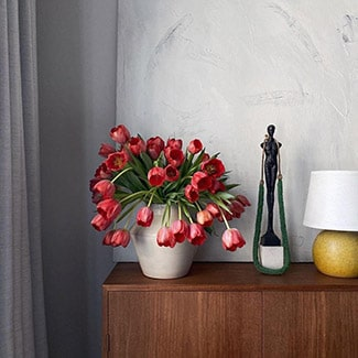 @indigo instagram post: White vase filled with red tulips on a wooden dresser. To the left of the vase is a sculptural figure in black and a yellow lamp with a white shade.