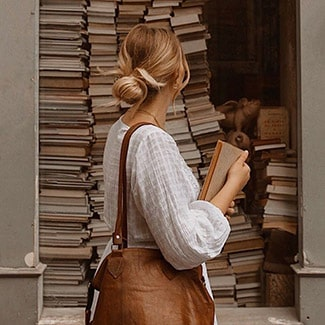 @indigo instagram post: Woman with blond hair in bun, white shirt, and brown bag facing away from the camera and looking at a big pile of books.
