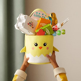 @indigo instagram post: Hands holding up a yellow chick-shaped Easter basket filled with gifts, including a Kid Made Modern craft kit, paints and paintbrushes, two activity books, a chocolate bunny, and the book Peek-A-Boo Little Chick by Yu-Hsuan Huang.