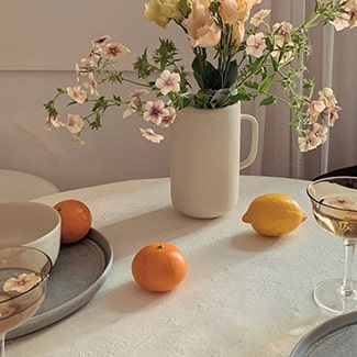 @indigo instagram post: White table topped with Oui organic stoneware, coupe glasses, two oranges, one lemon, and a Oui organic stoneware pitcher filled with flowers.