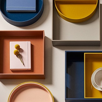 @indigo instagram post: Flat-lay of trays on a beige background. From top left to right: Oui Round Lacquer Tray in Blue Jay, Oui Half-Circle Tray in Sunflower inside a Oui Square Lacquer Tray Sahara, white mug and saucer inside a Oui Square Lacquer Tray in Sunflower sitting inside a Oui Rectangular Lacquer Tray in Blue Jay, pink round tray, pink notebook topped with yellow flowers inside a Oui Square Lacquer Tray in terrracotta.